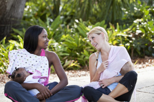 Multi-ethnic mothers chatting while nursing babies outdoors.