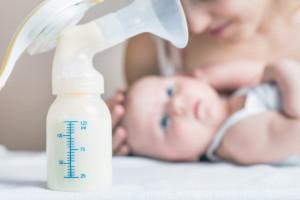 Extractor de leche manual, la leche materna es el alimento más saludable para el bebé recién nacido. Feliz, madre, con, bebé, en, plano de fondo
