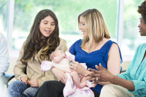 Beautiful Caucasian mom holds her infant daughter while talking with her peers during a meeting.